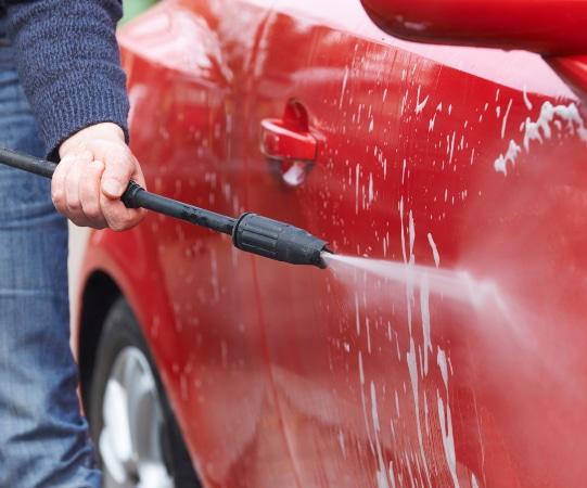 Limpiar coche rojo con hidrolimpiadora